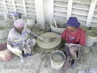Two Haitian women sifting the clay for t�